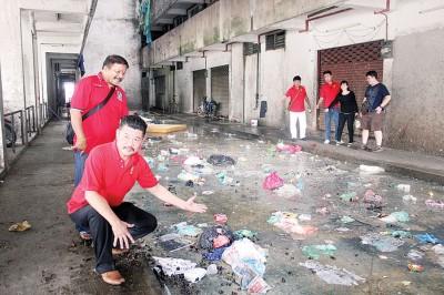 组屋天井处,可见垃圾堆积同时脏水也不断洒落,左1起苏巴拉及黄家业。