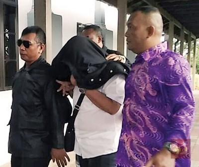 被告张鹏威以外套披在头部,并由随身保镖保护。