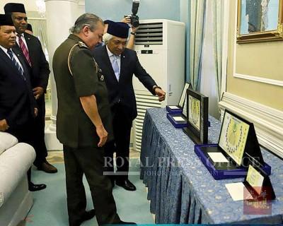 莫哈末依布拉欣(右起)向柔佛苏丹展示限量版纪念钞。