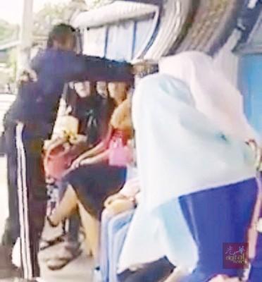 一名巫裔男子站在巴士站前因穆斯林女子没有穿戴头巾而当众推撞女子头部。(档案照)