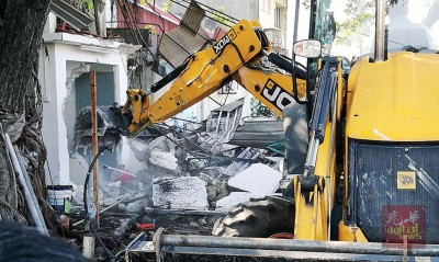 雄风省市政局动用掘土机拆除中心的初厕所。