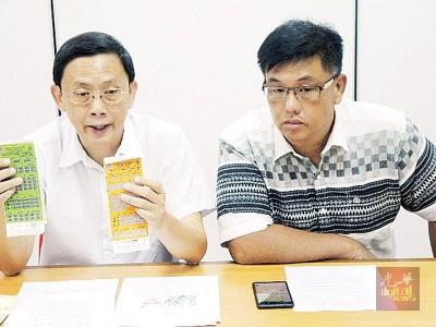 李文典(左)出示于今年杪必须用完的停车固本,右为民政党槟州亚依淡区协调员陈嘉亮。