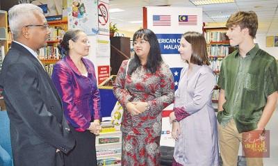 卡玛拉(左2)同美国中学交换生斯蒂芬妮(左3打)、艾米莉同查斯交流,左为沙希占陪同。