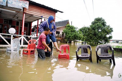 """水淹家园,甘榜古当拉骚的居民自行搭起""""椅桥""""成为出入的临时通道。柏腊河(Sungai Belat)泛滥已导致当地水淹5天。"""