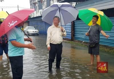 (左起)谢金荣、陈宗兴到巡视灾区,旁为甘榜德苏顺居民。