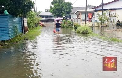 甘榜德苏顺一片汪洋,居民只能涉水外出买东西。
