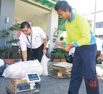 莫哈不赛夫(左)示范该企业如何将群众到来之回收物秤重量后,计算回酬费。