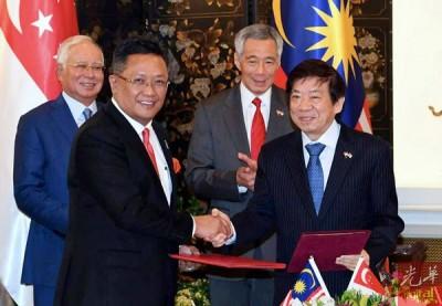 阿都拉达兰(前排左起)与许文远签署协议后,由纳吉(后排左起)与李显龙见证交换。