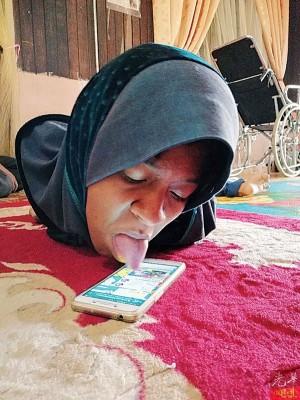 努莎玛娃蒂向本报记者示范如何以舌头滑手机。