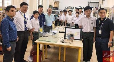 左起闻世荣、吴维城、江一德及江如松,右起许文龙及江一正,展示操作「水灾警报器」后合照。