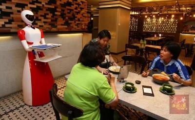 机器人走至餐桌前,为顾客送餐。