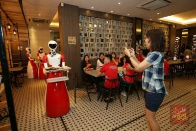"""女神帮机器人侍应生""""出动"""",吸引不少顾客竞相拍照。"""