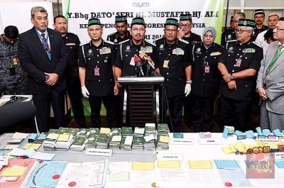 慕斯达法在记者会上展示当局从不法集团大本营起获的各种假护照、外劳卡和收据本等。