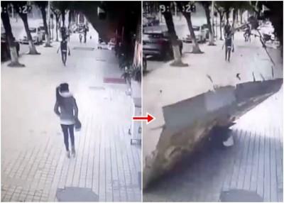 女子途经小食店门前,突然被倒塌的招牌当头砸中。