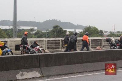 多名热心摩托车骑士,义务帮忙清理路旁垃圾,以避免淹水情况再发生。