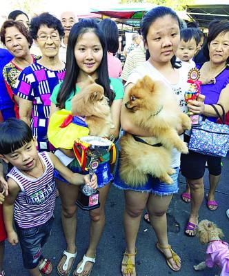 荣获冠军的Gucci狗狗(左)与高票胜出的明星狗Moses,在主人的拥抱下,一起合影。