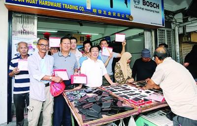 陈国伟(左4)视察年货摆卖市场并颁发执照予电子街业者。左3为蔡宝金。