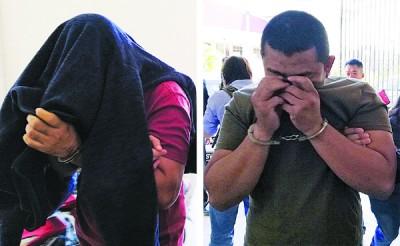 获保释候审的2名承包商以上衣和双手遮脸避开摄影镜头。