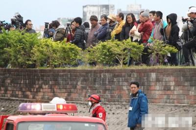 许多民众与搜救人员站在一起观看救灾进度。