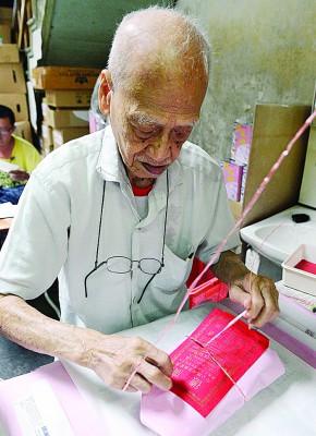 """""""广德""""腊味包装百年不变!胡树球亲自以粉红腊油纸及红纸包扎年货。"""