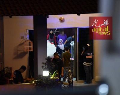 警方扣押穿紫色扣留服的女嫌犯在屋内进行调查。