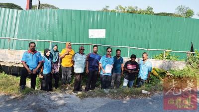 李文材(右4)以吃影响居民和务边国会选区服务队员的伴随下巡视下沉的路段。