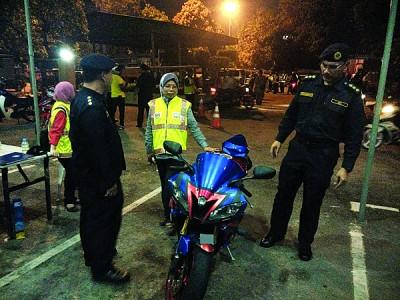 右1祖卡尼安向媒体展示所起获的复制摩托车。