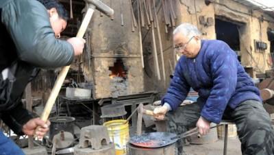 牛祺圣父子两人现场演示铁锅打造过程。