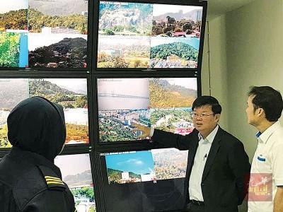 曹观友(右2)在槟岛市长尤端祥陪同下了解监查系统的运作。