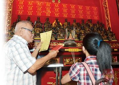 郭秋杉(左)为犯太岁者念出个人资料,向当值太岁祈福庇佑。