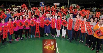 沈志强(右10自从)、章瑛、陈欣瀛以及具有参加者一起手举新春对联,贺大家春节快乐。
