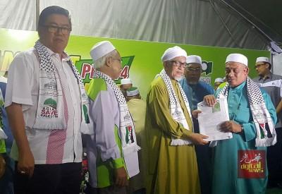 法兹(右)移交新党员入党表格予哈迪阿旺,左起范清渊、伊党峇东埔区部主席奥马哈山。
