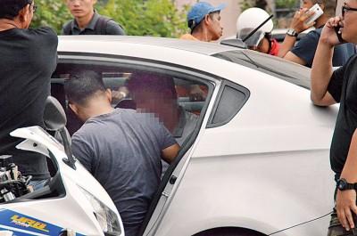 警方成功捉获一名匪徒,押上警车带走。