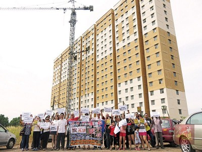 同多公寓买主不满发展商多年按照无学交屋,促请发展商早日全数归还买主已交的全套费用。(前排左5)也魏晓隆。