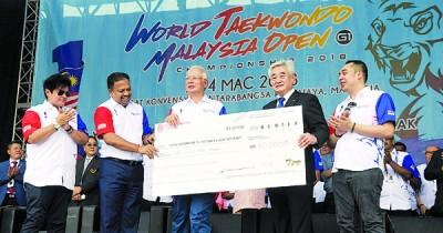 纳吉(倍受)见证维尼斯瓦兰(左2自打)移交6万令吉模拟支票予世界跆拳道联盟主席赵正源。
