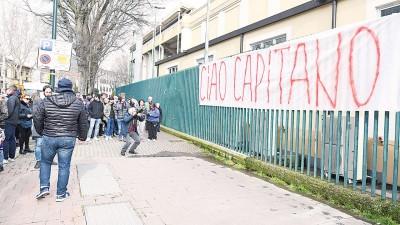 """一群球迷在弗连迪纳体育馆围栏前挂着写上""""再见!队长""""的巨大横幅悼念阿斯托里,有人还拿相机拍下横幅。"""