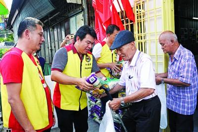 陈胤黇(左起)、江得瑋与众党员派发共100包米予亚依淡区居民。