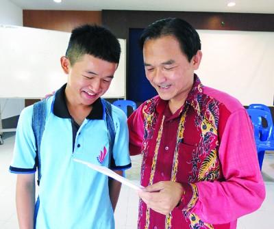 丘伟谦(左)与辅导老师苏培新分享成绩。