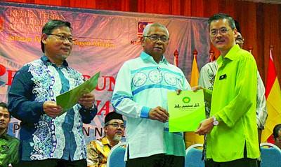末尤诺斯(中)颁发表扬状给表现卓越的学校之一的育民中学校长王大鹏。左为阿布峇卡。