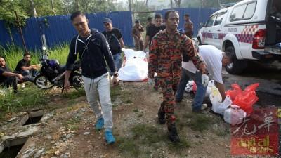 死者遗体被警官与消除员抬出来。