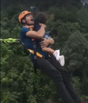 画面显示,在两人跃下的那一霎间,小孩背部看似有系上安全绳索。