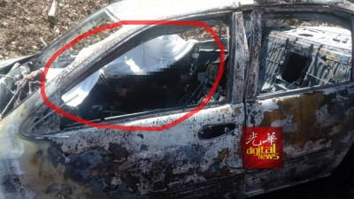 消拯人员在被烧毁的轿车驾座上发现一名烧成焦尸的司机。