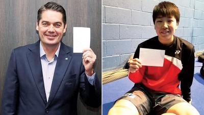 """世界羽联会长拉尔森(左)率先手举白卡,响应""""体育促进发展与和平国际日""""的和平讯息。日本女单名将山口茜(右)也手举白卡。"""