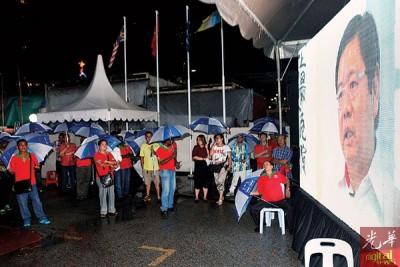 大雨驱不走民众,数百人涌入唯一的遮篷,继续聆听民政党领袖的讲座。