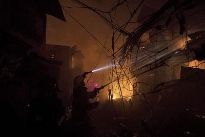 消防员手持电筒射水扑火。(法新社照片)