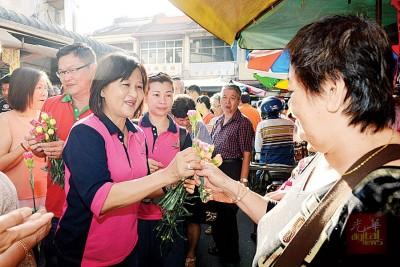 吴秀丽(左)趁着308国际妇女节为妇女们献上一朵花。