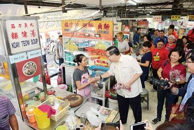 林冠英在当地饮食中心派发花束予民众及小贩。