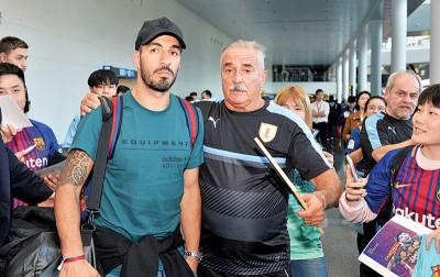乌推圭球星苏亚雷斯(右)到达北宁吴圩国际机场,遭到中国球迷热烈欢迎。
