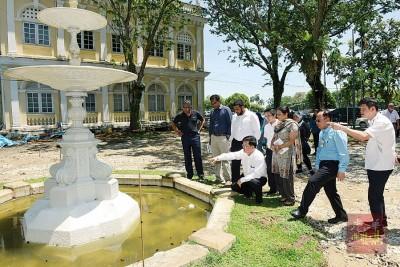 曹观友(蹲者)和一众官员一起观赏百年喷泉。