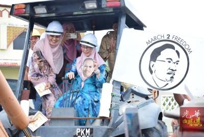 旺阿兹莎(坐者)手持安华肖像的面具,操控挖土机主持动土礼,长女努鲁依莎(前左)、次女努鲁努哈陪同。
